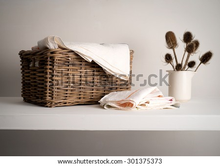 Wicker Basket with linen inside, on a shelf with a rustic bottle and dried teasel plant - stock photo