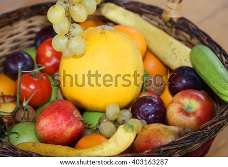 wicker basket with lots of fresh fruit in autumn and winter season - stock photo