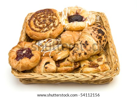 Wicker basket with selection of French & Danish pastries on white background. - stock photo