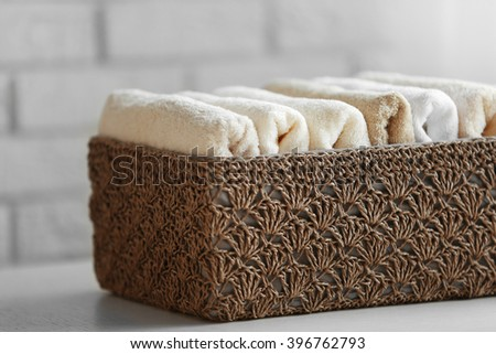 Wicker basket with towels inside on table, closeup - stock photo
