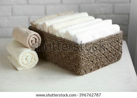Wicker basket with towels inside on wooden table background - stock photo