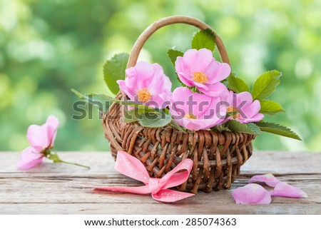 Wicker basket with wild rose flowers. Wedding or birthday decoration in rustic style. - stock photo