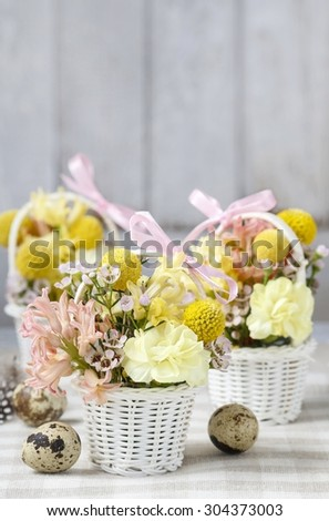 Wicker baskets with early spring flowers, easter decorations - stock photo