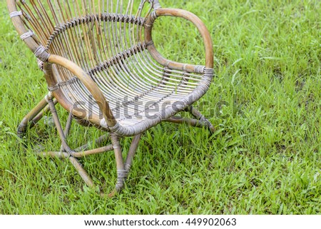 Wicker chair in the garden and green grass. - stock photo