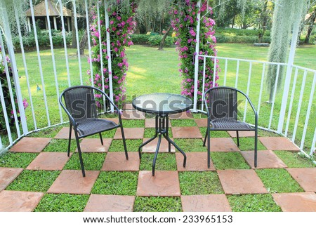 Wicker chair in the garden decorated with tiled floor - stock photo