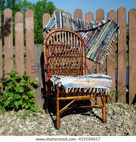 Wicker chair on the wooden fence - stock photo