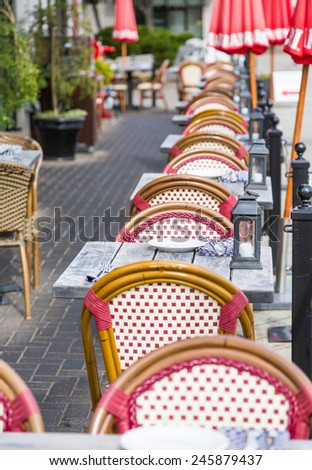 Wicker chairs and wood tables at an outdoor restaurant patio - stock photo