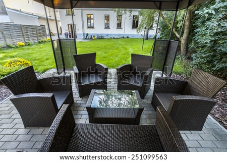 Wicker chairs on hotel's patio in garden - stock photo
