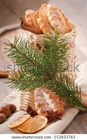 Wicker Christmas stocking filled with cookies, cinnamon sticks, candied lemon and star anise - stock photo