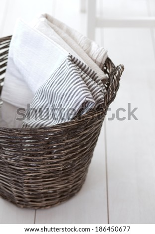 Wicker clothes basket with cotton linen in it - stock photo
