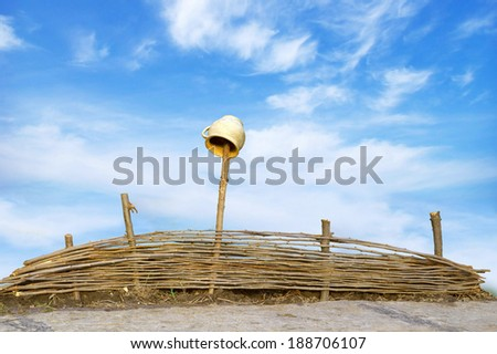 Wicker fence of thin rods with old clay pot hanging to dry on a wooden column, standing near the road, isolated with clipping path on blue sky backdrop with space for text - stock photo