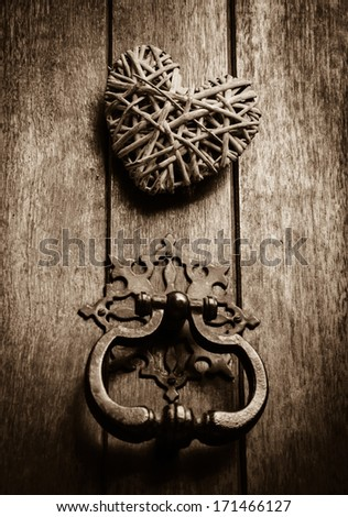 Wicker heart on old wooden door with ornate doorknocker. Sweet home background. Sepia. Shadowed angles. Retro style greeting card.  - stock photo