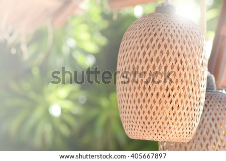 Wicker lamp shade against a background of garden - stock photo