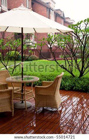 Wicker patio chairs and table near garden on rain - stock photo