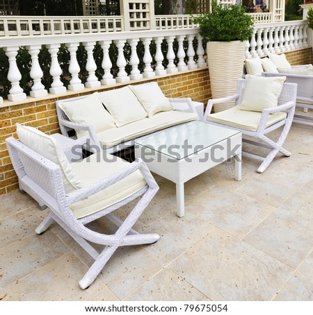 Wicker patio furniture outdoor in area paved with natural stone - stock photo