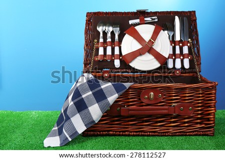 Wicker picnic basket on green grass on blue background - stock photo
