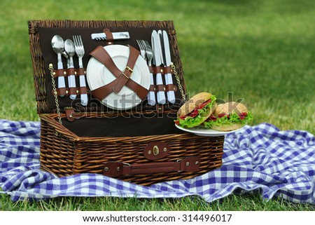 Wicker picnic basket, tasty sandwiches  and plaid on green grass, outdoors  - stock photo