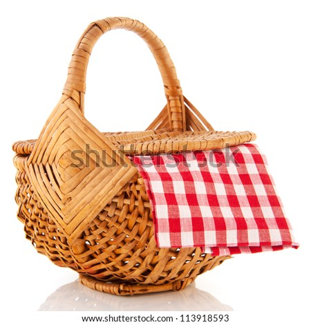 Wicker picnic basket with checkered red and white table cloth - stock photo