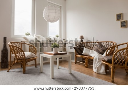 Wicker sofa and chairs in living room - stock photo