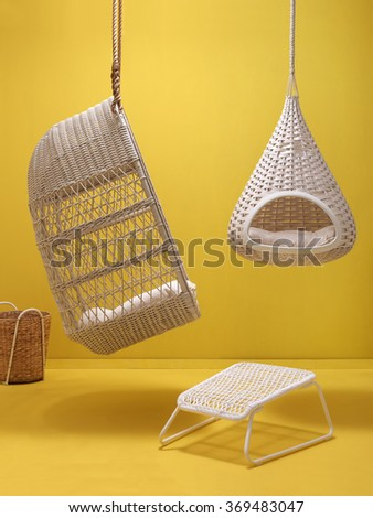 wicker swing and vertical yellow background - stock photo