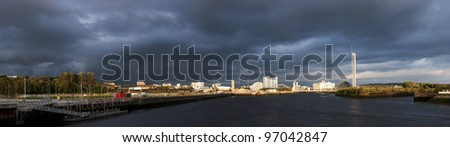 Wide and high resolution panorama of River Clyde in Glasgow showing lndmarks glowing in sunlight as stormy clouds loom. - stock photo