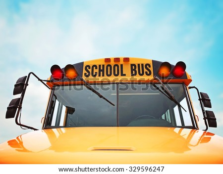 wide angle front view of a bright yellow orange school bus on a sunny summer day with clouds in the sky toned with a retro vintage instagram filter app or action effect - stock photo
