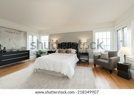 Wide angle of light olive bedroom with white sheets, night stands wooden floor and natural fibers rug. - stock photo