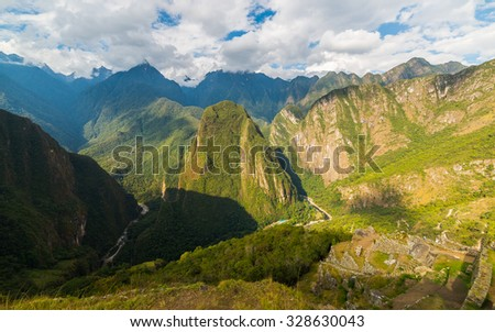 Wide angle panoramic view from Machu Picchu, illuminated by afternoon sunlight, over the majestic Urubamba Valley with dramatic sky. - stock photo