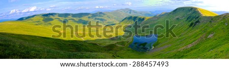 wide angle panoramic view on the glacier lake and valley in Ukrainian Carpathians - stock photo