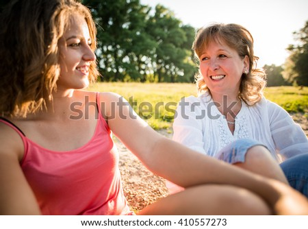 Wide angle photo of teen girl with her mature mother talking together, outdoor in nature - stock photo
