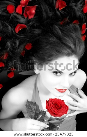 wide angle portrait of pretty woman with red dress rose and petals - stock photo