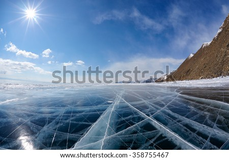 Wide angle shot of winter ice landscape on Siberian lake Baikal with dramatic weather clouds on blue sky background - stock photo