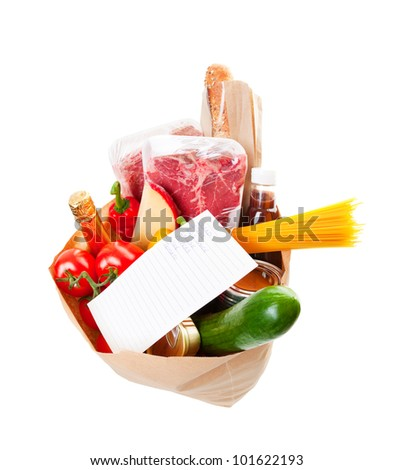 Wide angle view of a grocery bag full of barbecue staples with a hand written grocery list on top. - stock photo