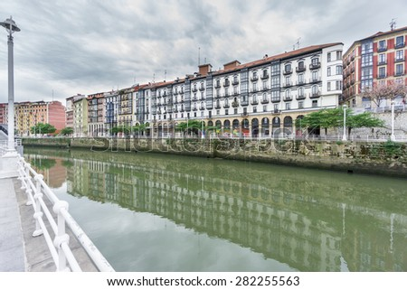 Wide angle view of Bilbao la vieja and Nervion river with cloudy sky - stock photo