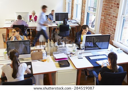 Wide Angle View Of Busy Design Office With Workers At Desks - stock photo