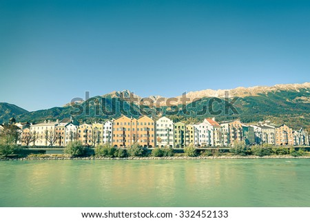 Wide angle view of Innsbruck with Tirol mountains on background - Colorful buildings among Inn riverbank in Austria - Vintage retro filtered look with main focus on central houses - stock photo