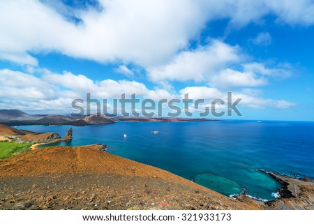 Wide angle view of the Pacific Ocean around Bartolome Island with Pinnacle Rock on the left side in the Galapagos Islands in Ecuador - stock photo