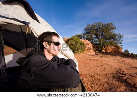 Wide angle view of young man sitting inside tent in Arizona desert. Outdoor adventure/camping concept. - stock photo