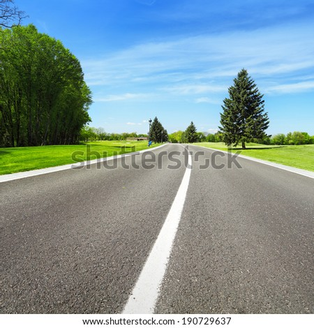Wide asphalt road and green trees on blue sky background - stock photo
