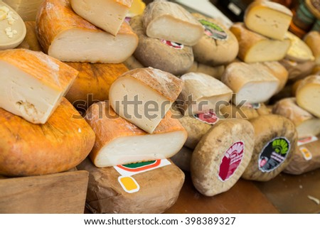 Wide assortment of delicious cheese in display of food store - stock photo