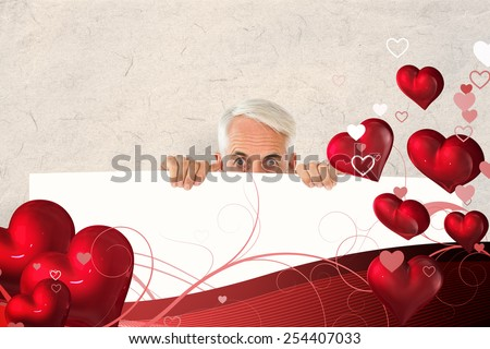 Wide eyed man showing large poster against parchment - stock photo