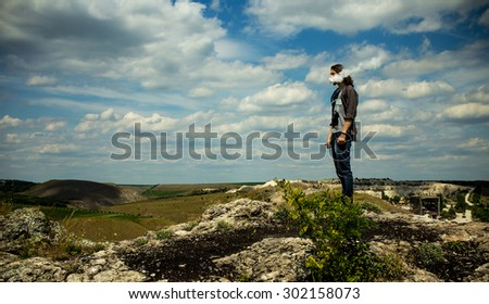 Wide image of man vaping electonic cigarette and staying on rocky hills against blue cloudy sky. With vignette. - stock photo