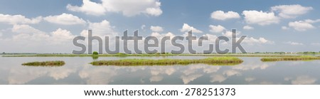 wide lagoon with sky reflexion in summer - stock photo