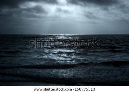 Wide minimalist view of ocean glistening in the horizon with sunbeams in the sky - stock photo
