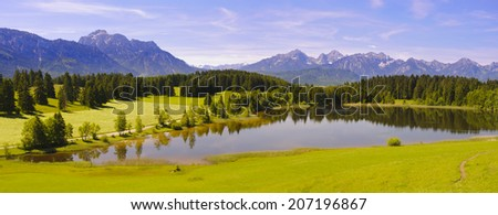 wide panorama landscape in Bavaria with lake and alps mountains nearby city Fuessen - stock photo
