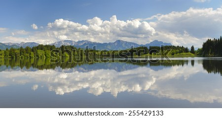 wide panorama landscape with lake Forggensee and alps mountains in Bavaria, Germany - stock photo