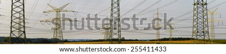 wide panorama view to many electric pylons in germany - stock photo
