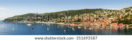 Wide panoramic view of French Riviera coast at Villefranche-sur-Mer harbour and Cap de Nice with leisure boats anchored at Mediterranean sea - stock photo