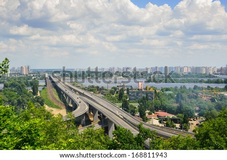 Wide river is dividing the city into right and left riverside. Both banks are overgrown with green trees and bushes. A modern bridge recedes into the left-bank residential district and the cloudy sky. - stock photo