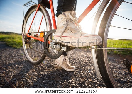 Wide shot of the foot on pedal of retro orange bicycle at sunset in countryside. Active summer. Vintage feeling. Low depth of field. Strong sun and dark long shadows. - stock photo